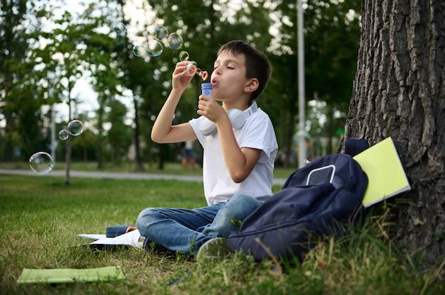 Школьник младших классов отдыхает в парке, сидит на зеленой траве после школы и пускает мыльные пузыри. школьная сумка с учебниками и школьными принадлежностями, лежа на траве