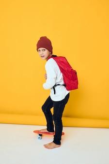 男子生徒は黄色の背景のスケートボードに立っています