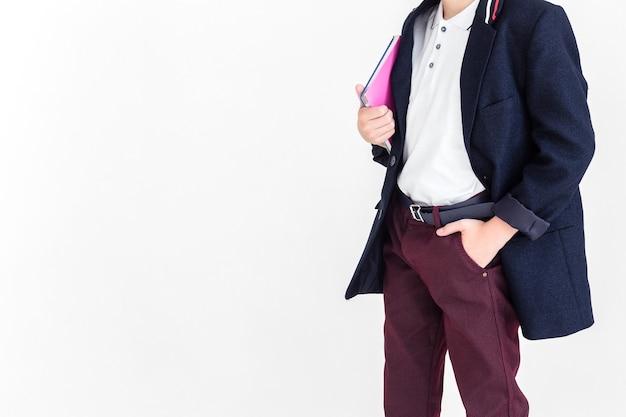 Школьник стоит на белом фоне в брюках школьной формы куртке и рубашке мальчик хо ...