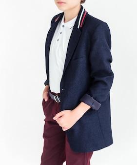 Школьник стоит на белом фоне в брюках школьной формы, куртке и рубашке