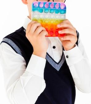 Школьник с хлопушкой в руках стоит на белом фоне в школьной форме