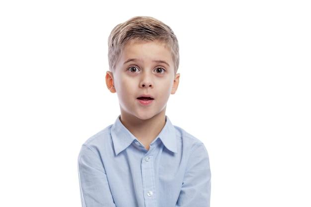 불룩한 눈과 입을 벌리고있는 남학생이 놀란다. 흰색 배경에 고립.