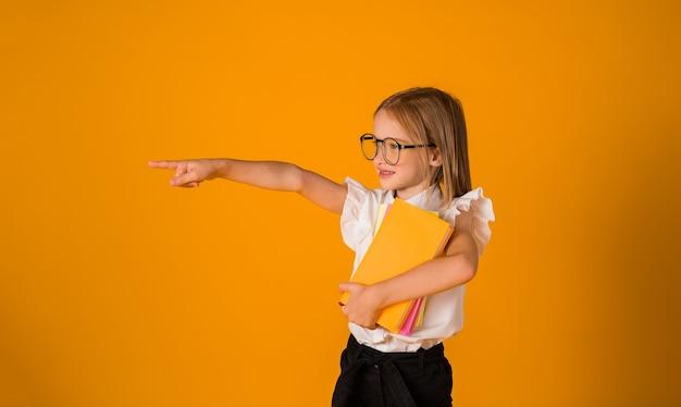 교복을 입고 안경을 쓴 한 여학생이 노란색 배경에 텍스트를 넣을 수 있는 곳이 있는 쪽을 가리키고 있습니다.