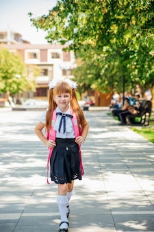 Школьница в белой блузке и черной юбке с портфелем идет по переулку или по улице. девочка ходит в школу или домой после уроков.