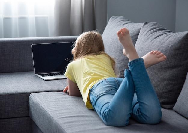 청바지 여학생과 컴퓨터에서 온라인 수업을보고 집에서 소파에 노란색 티셔츠. 코로나 바이러스 동안 원격 학습