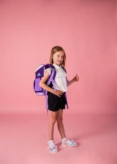 制服を着たフルレングスのバックパックを持った女子高生は、ピンクの背景にクラスを示し、手でスペースのコピーを持っています