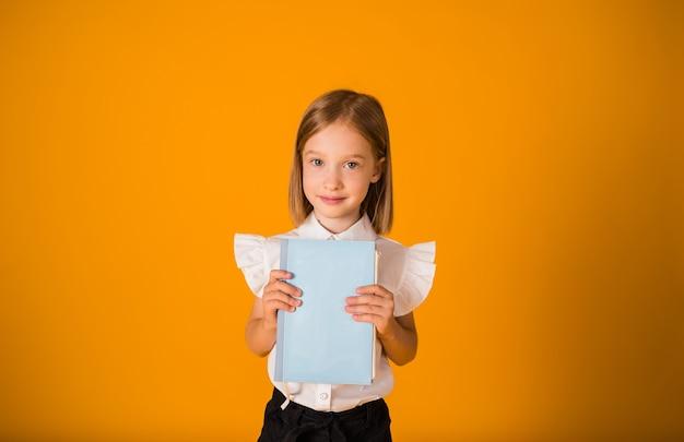 제복을 입은 여학생이 노란색 배경에 파란색 공책을 들고 공간 사본을 들고 서 있습니다. 학교로 돌아가다