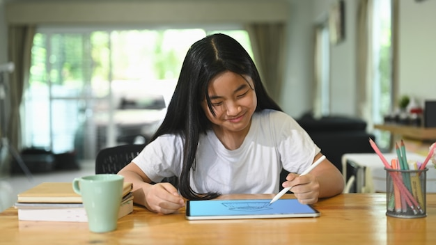 女子高生は、木製のワーキングデスクでコンピュータータブレットを使用してeラーニングを行っています。