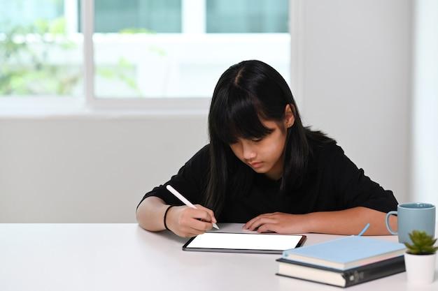 Школьница с помощью цифрового планшета делает домашнее задание онлайн дома. онлайн-образование, обучение на дому, концепция домашнего обучения.