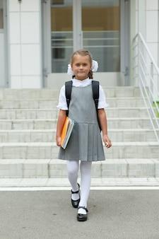 Рядом со школой идет школьница с учебниками и рюкзаком.