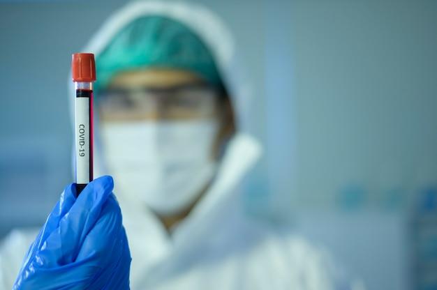 Ученый, держащий жидкую химическую трубку в лаборатории