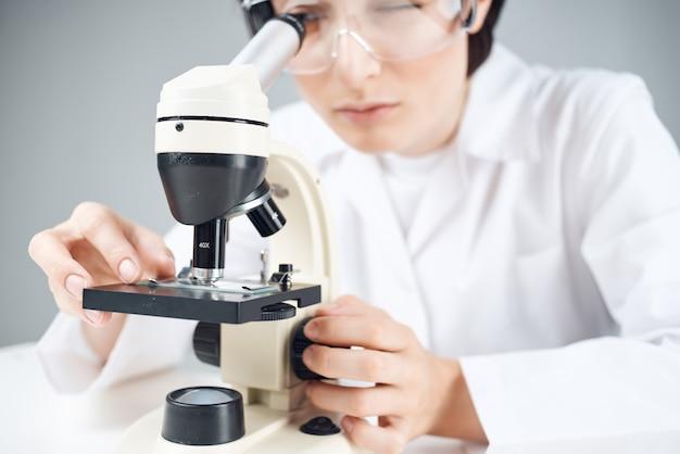 현미경 근접 촬영 실험실을 들여다보고 있는 흰색 코트를 입은 과학자