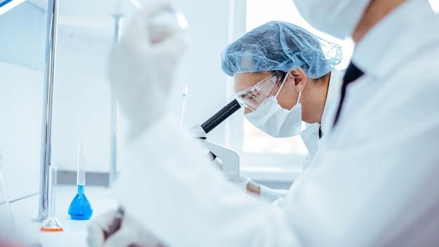 Ученый смотрит на бутылку с новой вакциной