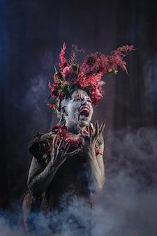 Кричащая девушка, намазанная глиной, в зацементированном платье. у модели головной убор из цветов. дым сзади.