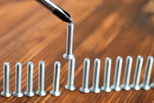 Отвертка с магнитной насадкой крепит винт к стене ряда шурупов и деревянной стене
