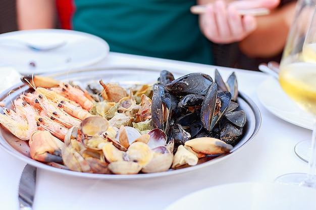 Блюдо из морепродуктов заделывают. ассорти из морепродуктов в ресторане.