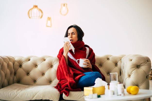季節性インフルエンザ。赤い毛布で覆われた、自宅で病気に苦しんでいる、お茶を飲んでいる咳をしている女の子のクローズアップ。