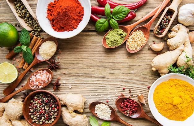 그릇과 숟가락에 나무 테이블에 다양한 다채로운 향신료의 선택