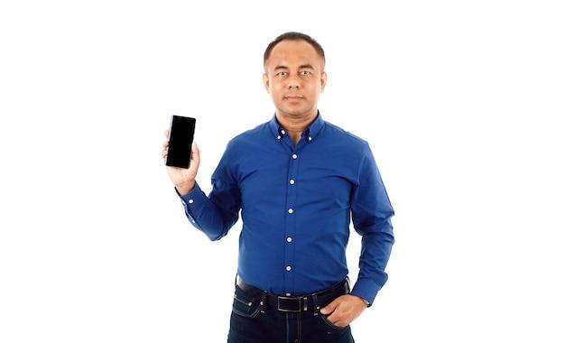 Уверенный в себе мужчина среднего возраста старший азиатский в синей деловой повседневной рубашке, держащей смартфон. изолировать на белом фоне.