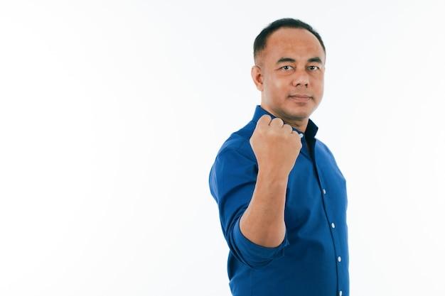 青いビジネスカジュアルシャツを着た自信のある中年シニアアジア人男性が立って、コピースペースで強い拳パンチを示しています。手に選択的な焦点。