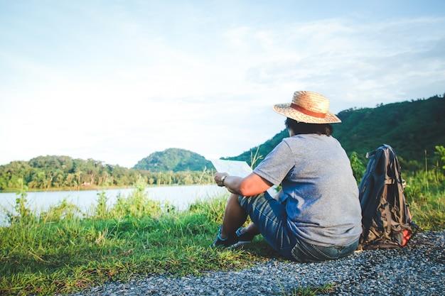 上級アジアの女性が自然観光の地図を見るために草の上に座っている帽子をかぶっています。