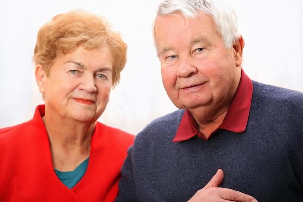 Старшая пара стоя на белом фоне