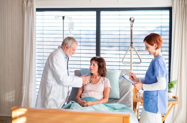病院で女性患者を診察する先輩医師と看護師。