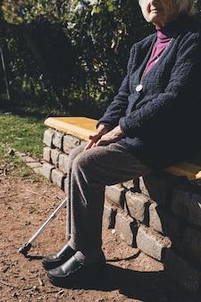 Старший леди, сидя на скамейке в парке на солнце.