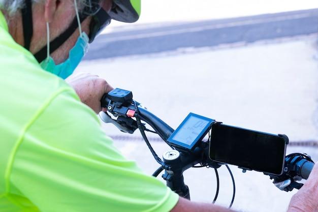 안전을 위해 노란색 헬멧을 쓰고 전기 자전거를 운전하는 노인. 코로나바이러스 코비드-19의 전염을 피하기 위해 의료용 마스크를 착용합니다.