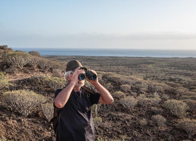 Старший мужчина, походы в засушливый вулканический ландшафт. глядя в бинокль. молодые люди пожилого возраста, наслаждающиеся здоровым образом жизни. горизонт над водой. свет заката
