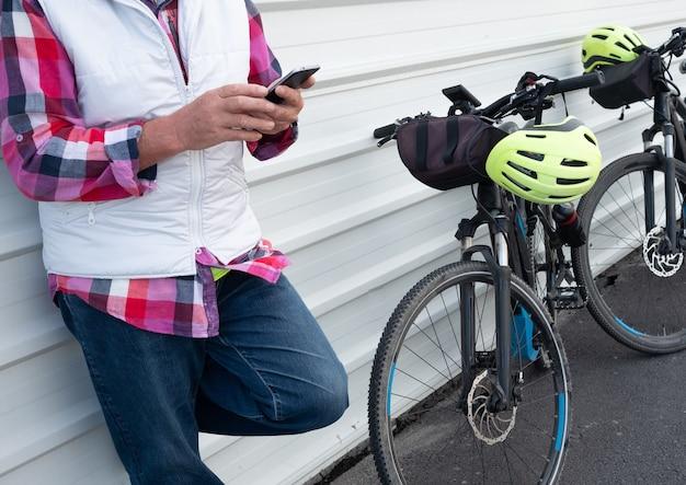 흰색 금속 벽에 서 있는 수석 남자. 그의 휴대 전화를 찾고. 그의 전기 자전거 검은 색과 노란색 헬멧을 가진 활동적인 사람들