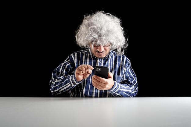Старший мужчина, типичный бумер, изогнулся на своем смартфоне, набирая текстовое сообщение