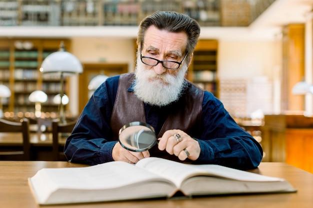 Старший человек, профессор университета, ученый, с белой бородой и очками сидит за столом в большой библиотеке, изучает книгу с помощью увеличительного стекла.