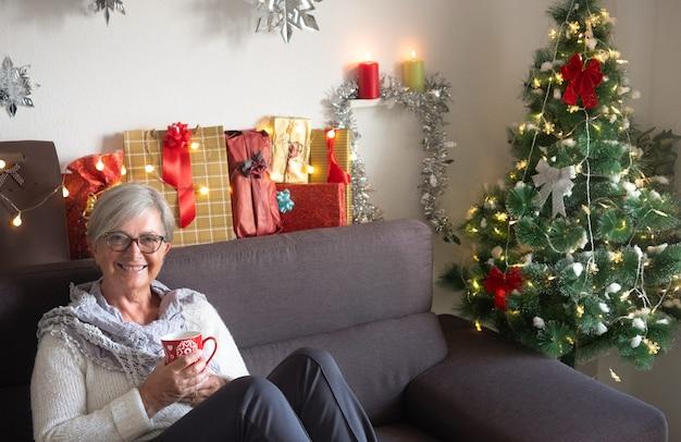 お茶を飲みながらソファでくつろぐ年配のきれいな女性。カメラを見て、笑っています。彼女の周りのクリスマスツリーとギフト