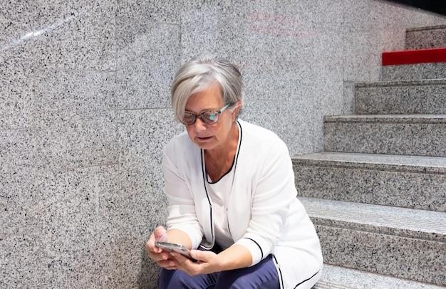 携帯電話を使って階段に座っている年配の女性。メッセージに焦点を合わせます。白髪の美しい人