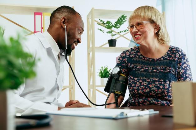 Пожилая женщина посещает терапевта в клинике