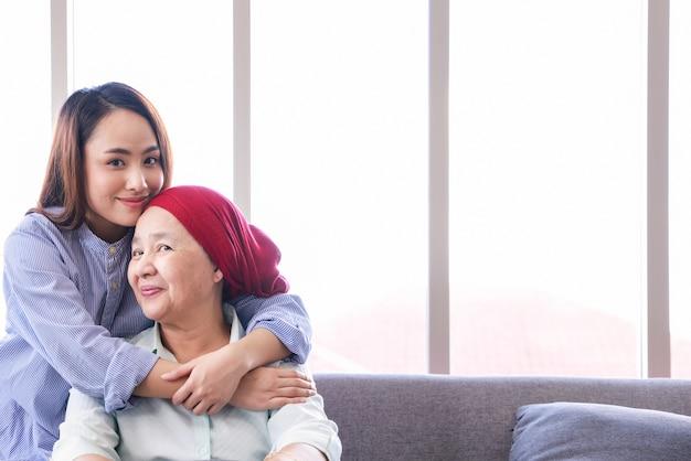 がんの年配の女性が大人の娘と一緒に家でくつろぐ。女性たちは未来への希望に満ちている。