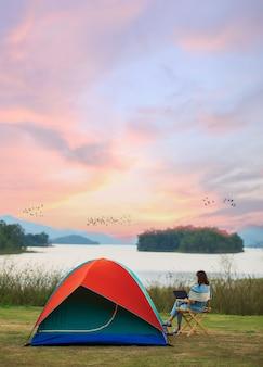 캠핑 텐트 옆에 앉아 호수 쪽에서 작동하는 노트북 랩톱 컴퓨터를 사용하는 여성 여행자의 평화와 평온의 감각 사진. 화려한 하늘을 나는 새들의 무리가 있습니다.