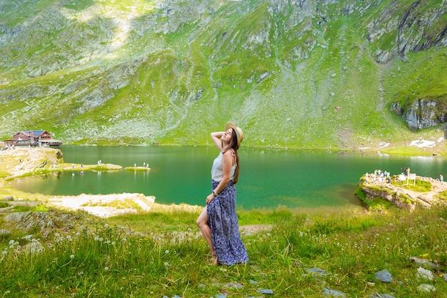 긴 드레스와 밀짚 모자를 입은 관능적 인 여성이 루마니아 산의 balea 호수 기슭에 서 있습니다.