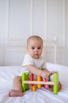 Серьезная девочка в белом боди с кружевом играет с развивающей игрушкой на кровати