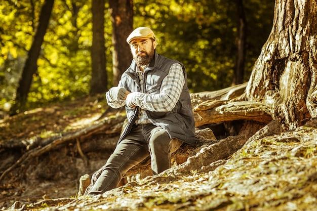 좋은 하루에 숲에서 나무 옆에 앉아 심각한 수염 남자