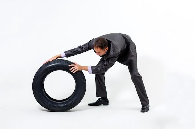 Серьезный бизнесмен с автомобильными шинами. ремонтная мастерская. автосервис. перепродажа запчастей. solated на белом фоне