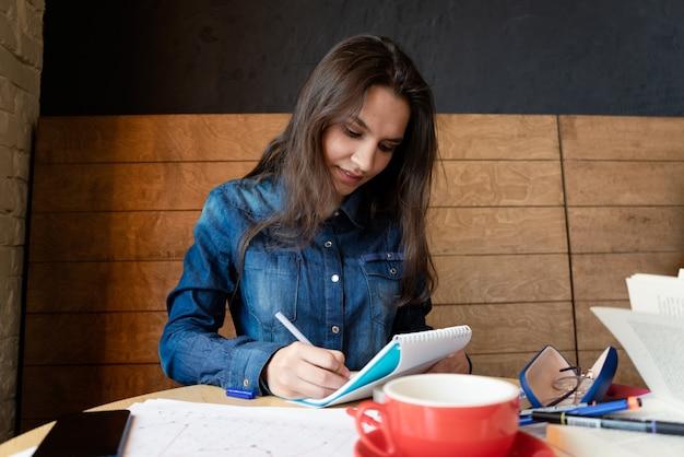 Серьезная девушка в синей джинсовой рубашке сидит в кафе, делает пометки в блокноте ручкой. на столе листы бумаги, смартфон, очки в футляре, скотч, фломастеры.