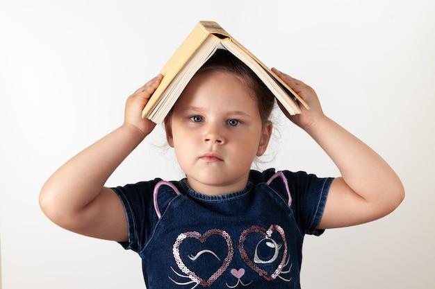 Серьезная девушка в джинсовом платье держит над головой книгу, ребенок изолирован.