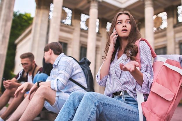 真面目な女の子が電話で対話者から何かを見つけようとしています