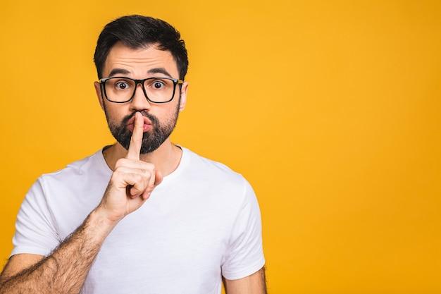 真面目なハンサムな男は、前指を唇につけ、陰謀を続けようとします、と言います:ああ、静かにしてください。
