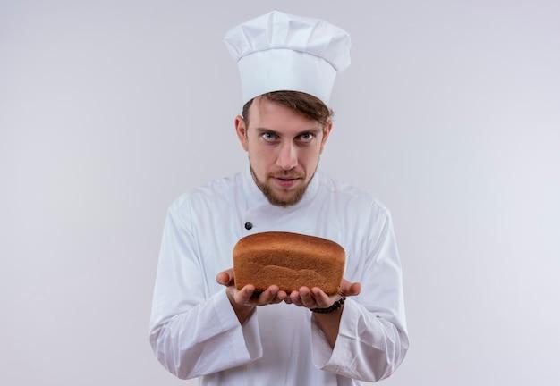 白い壁を見ながらパンの塊を示す白い炊飯器の制服と帽子を身に着けている真面目なハンサムな若いひげを生やしたシェフの男