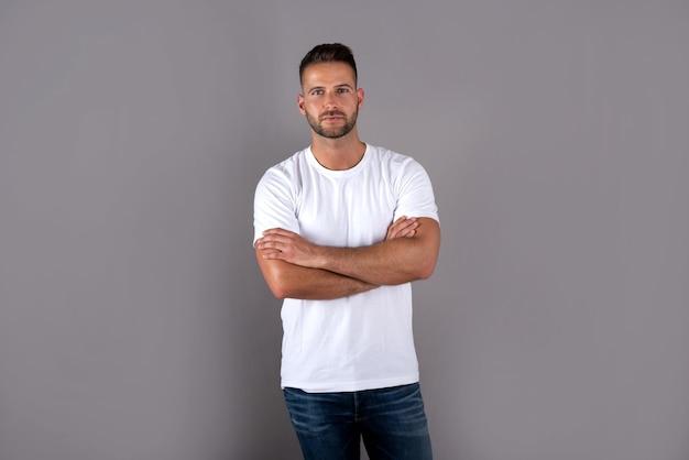 Серьезный красивый молодой человек в белой футболке стоит на сером