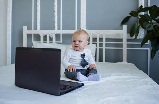 Серьезный мальчик в костюме сидит на кровати с ноутбуком