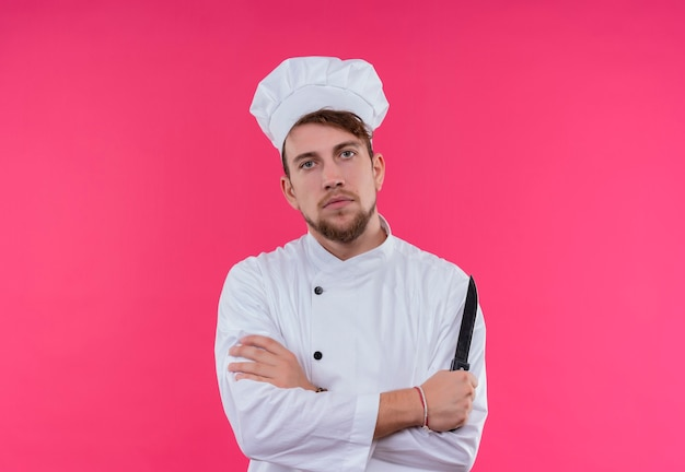 ピンクの壁を見ながらナイフを持っている白い制服を着た真面目な若いひげを生やしたシェフの男